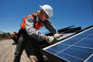 worker installing solar panels and a 3 phase inverter