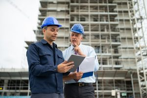 Two engineers using construction software programs in a tablet
